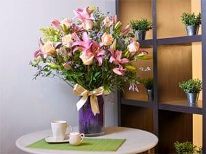Florero rosas lirios lisianthus con malla fina y cinta de raso