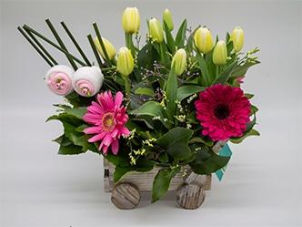 Bebe, arreglo floral de tulipanes y gerbera sobre carro artesanal de madera