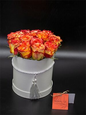 Rosas amarillas con borde anaranjada en sombrerera blancas