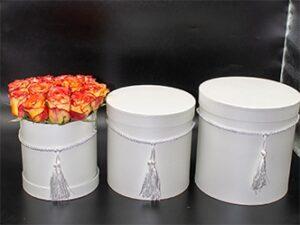 Rosas en tres tamaños de sombrereras blancas