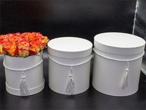 Rosas en tres tamaños de sombrereras blancas elegante